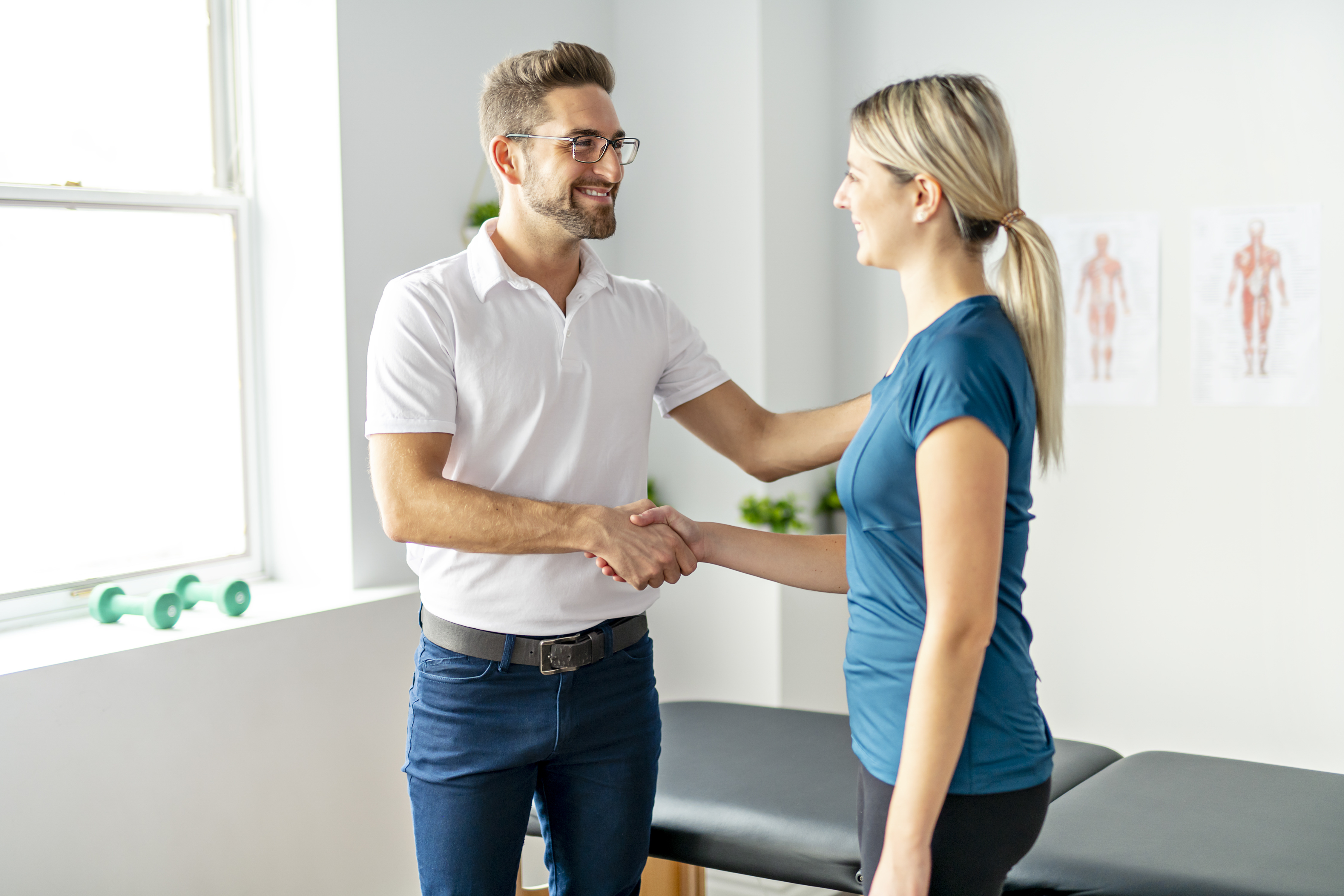A Modern rehabilitation physiotherapy man at work with woman client hand shake